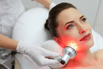 Facial Beauty Treatment. Woman Doing Red Led Light Therapy