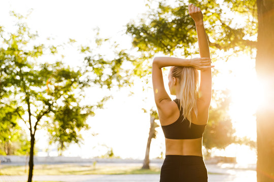 Beautiful young blonde sports woman in park outdoors make stretching exercises.