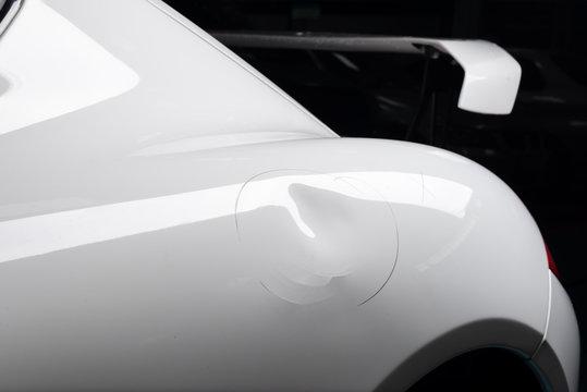 Auto body repair series: Dent on white sports car