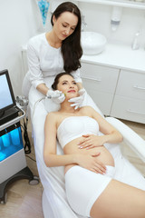Beauty Clinic. Pregnant Woman Doing Intense Peeling Treatment