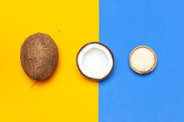 Organic cosmetics with coconut oil, ripe coconut on yellow and blue colored background top view minimal flat lay style. Coconut shavings, oil, milk. Healthy skincare. Homemade cosmetic and spa care.