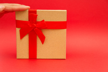 gift box with red ribbon on red background with copy space
