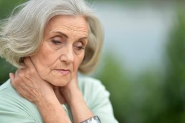 Portrait of sad elderly woman posing outdoors