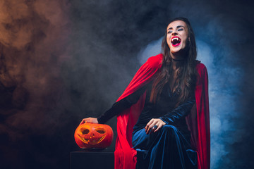 beautiful woman in vampire costume smiling on dark background with smoke