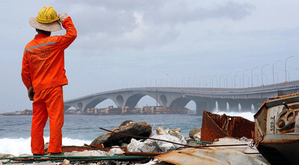 A construction worker looks on as the China-funded Sinamale bridge is seen in Male