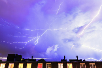 Thunder flashes in the sky over Amsterdam during a heavy thunderstorm in summer