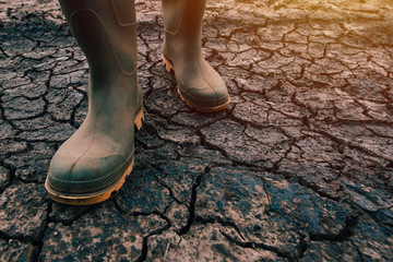 Farmer in rubber boots walking on dry soil ground