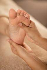 Masseuse massaging female foot at the spa.