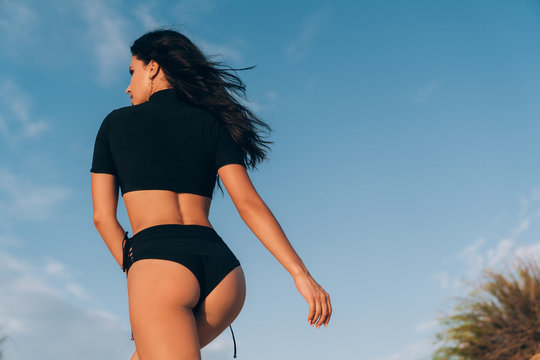 Rear view of a close-up ass of a beautiful slender young girl in a swimsuit. The model goes up, the face in profile, curly dark hair blows the sea breeze.