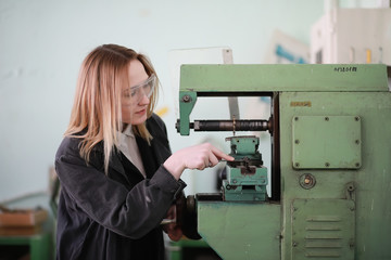 Young woman engineer working at machine tool