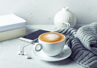 Cup of cappuccino coffee, a warm gray cloth, a smart phone and books on gray background. Close-up. Copy space