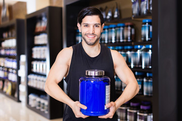 Young bodybuilder showing power and holding pot  of sport nutrition products in shop
