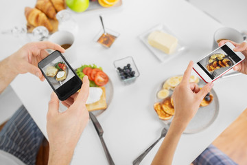 food and technology concept - close up of couple with smartphones having breakfast at home