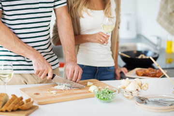culinary and healthy eating concept - close up of couple cooking and drinking non alcoholic wine at home kitchen