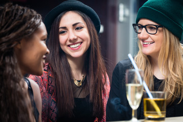 Three smiling female teenage friends looking at each other with glasses of drinks on table at restaurant