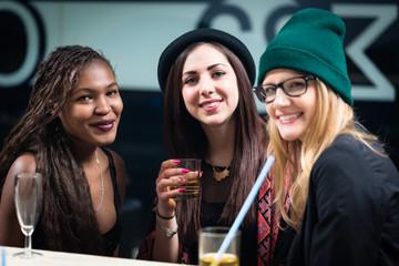 Three female diverse friends enjoying drinks on the restaurant