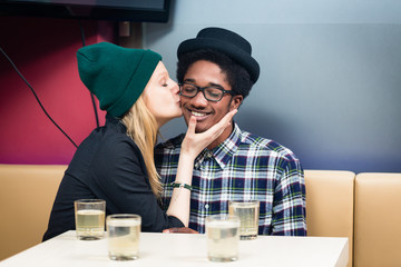 Close-up of girlfriend kissing her smiling boyfriend siting in the restaurant