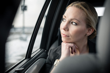 Thoughtful businesswoman travelling in car looking through car window