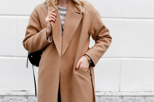 Beautiful young stylish blonde woman wearing beige coat and black backpack posing near white street wall. Trendy casual outfit. Street fashion. Details of everyday look.