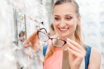 Beautiful woman in optician store chooses her glasses looking pleased