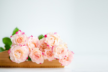 pink roses on a wooden tray