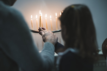 Father and daughter putting candle in menorah