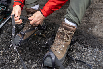 Close up cropped photo of alpinist man pull sling on anti-slip hiking crampons device, focus on shoelace professional boots with vibram sole base stand on dirty