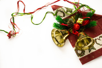 Gold christmas bell on red napkin with branches of fir tree, red ball and yellow gifts isolated on white. Christmas and New year theme and symbols. Winter holidays. Gold, red, green and red colors.