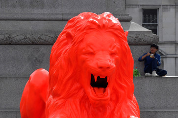 An orange painted lion, designed by artist Es Devlin, which forms part of the London Design Festival, is displayed in Trafalgar Square, London