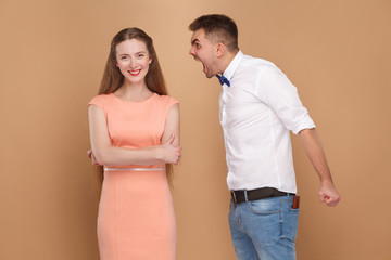 Crazy young man in white shirt standing and screaming at woman in pink dress. woman dont care and looking at camera with toothy smile. indoor studio shot, isolated on light brown background.