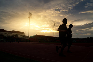 Men people runs at the stadium on beautiful sunset. Silhouette picture of runners on sunset background, wellness concept.