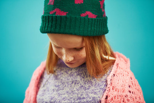 Portrait of sad child girl in winter clothes lowered his head down. Upset kid because onset cold weather.