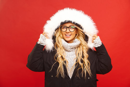 Portrait of satisfied woman, wearing a warm winter jacket with hood, has joyful expression, feels warm and comfortable in new clothes, stands on red isolated.
