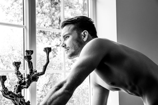 Hunky muscular, sexy shirtless man with defined abs and muscles looks out of window