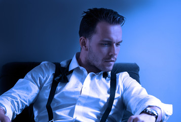 Man wearing tuxedo in hotel room, sitting in chair with loose tie