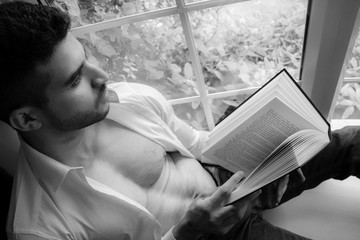 Man in sitting on window ledge with open shirt and pecs reading hardback book