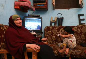 Heba Mahmoud, who is visually impaired, sits next to her daughter as she watches television in Cairo