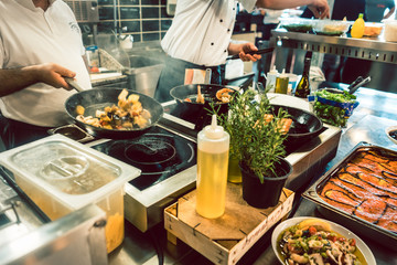 High-angle view of various fresh ingredients on the stove and the counter of a commercial kitchen in a trendy restaurant with fish specialties