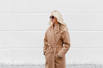 Beautiful young stylish blonde woman wearing beige coat and black sunglasses standing near white street wall. Trendy casual outfit. Street fashion.