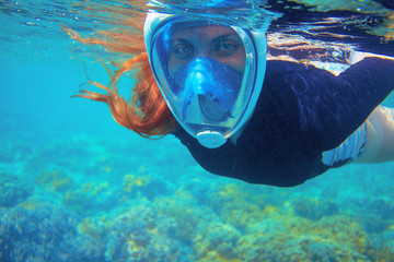 Red hair snorkeling girl full-face snorkeling mask in coral reef. Snorkel in coral reef of tropical sea.