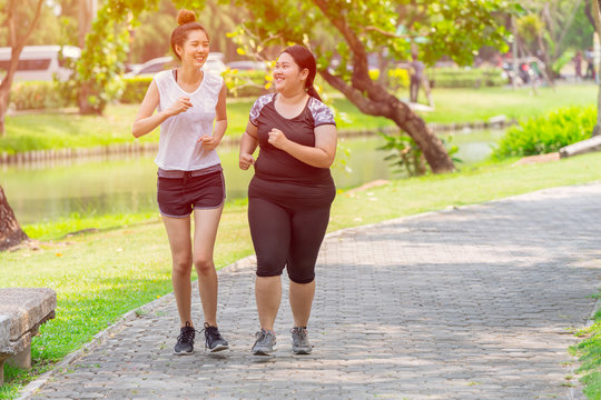 Asian two thin and fat girls friend running jogging park outdoor in the morning