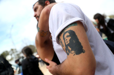 Supporters of former Argentine President Fernandez de Kirchner, one of them with a tattoo of her portrait, embrace after she left the Federal Justice building in Buenos Aires