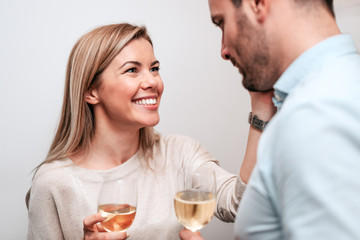 Smiling couple drinking white wine and cuddling. Close-up.