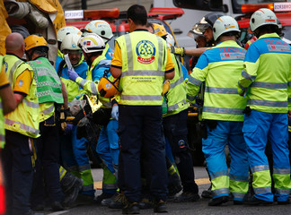 Emergency workers evacuate an injured worker following a building site collapse at Madrid's Ritz Hotel in Madrid