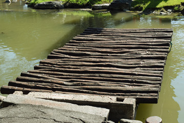 antique wooden embankment near the river in the park