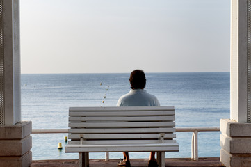 Pensive man on a bench by the sea
