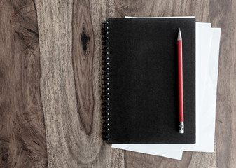 directly above shot of black spiral notebook and pen on wooden table