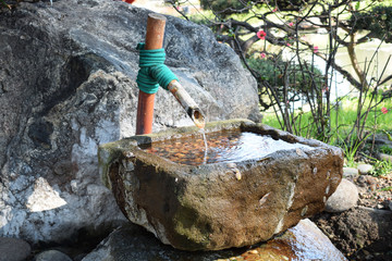 a bamboo faucet to drink water in the park