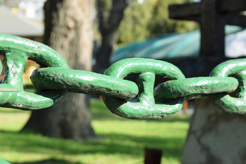 thick antique chain painted in green light in a park