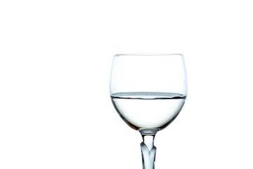 Water in a wine glass close up, isolated on white background.
